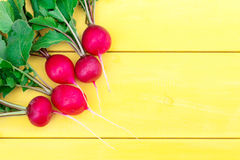 A bunch of radishes on a wooden table. Five radishes with tops lie on a wooden table. The objects are in the upper left corner Stock Photo