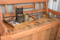 A bunch of random trinkets placed on a bright wooden bench. stock image