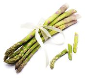 Asparagus. Bunch of raw asparagus tied with a creamy knot and three cut pieces isolated on white backgroundn Stock Photography