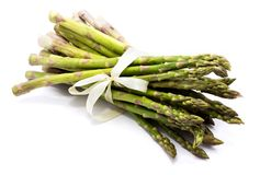 Asparagus. Bunch of raw asparagus tied with a creamy knotbow isolated on white backgroundn Stock Image