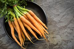 Bunch of Raw Baby Carrots in Rustic Black Bowl over Slate. Background stock photo