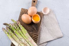 Bunch of raw fresh garden organic asparagus with eggs on wooden board. Top view Royalty Free Stock Image
