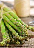 Bunch of raw, green asparagus. On wooden table Royalty Free Stock Photos