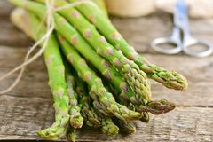 Bunch of raw, green asparagus. On wooden table Stock Image