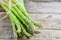 Bunch of raw, green asparagus. On wooden table Stock Photo