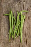 Bunch of raw green beans. On old wooden table Stock Images