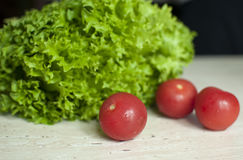 Bunch of raw organic green frisee salad and two tomatoes Royalty Free Stock Photo
