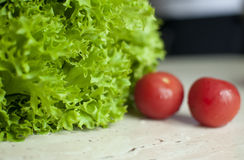 Bunch of raw organic green frisee salad and two tomatoes Stock Photo