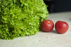 Bunch of raw organic green frisee salad and two tomatoes Stock Image