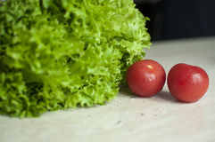 Bunch of raw organic green frisee salad and two tomatoes Royalty Free Stock Photos