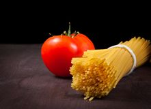 Bunch of raw pasta spaghetti  with tomato on wood table Stock Images