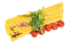 Bunch of raw spaghetti with garlic and tomato Royalty Free Stock Image