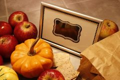A bunch of red apples lies next to a miniature pumpking. A framed blank chalkboard sign stands in the middle stock photo