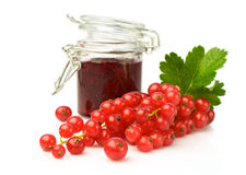 Bunch of red currant and glass jar with jam Stock Images