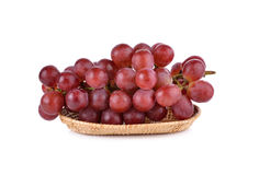 Bunch of red grape in rattan basket on white Royalty Free Stock Image
