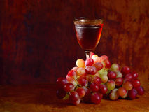 Bunch of red grape and wine glass. On a wooden tray stock photography