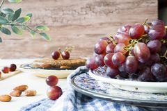 Bunch red grapes in blue  bowl, against wooden background royalty free stock photography