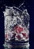 Bunch of red grapes falling down in water Royalty Free Stock Image