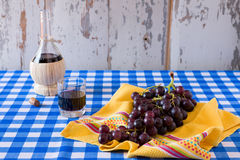Bunch of red grapes and a glass of red wine. With a wine flask on a checkered tablecloth Royalty Free Stock Images