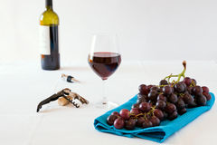 Bunch of red grapes and a glass of red wine with a wine bottle Stock Photography