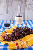 Bunch of red grapes and a glass of red wine with a wine flask. On background over a checkered tablecloth Royalty Free Stock Images