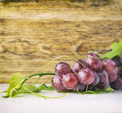 Bunch of red grapes and leaves and wooden pattern Royalty Free Stock Photo