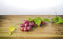 Bunch of red grapes and leaves on wooden table Stock Photos