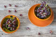 Bunch of red grapes in orange bowl, against wooden background royalty free stock photography