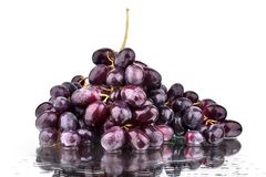 Bunch of red grapes on a white mirror background with reflection and water drops isolated close up stock photo