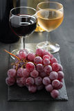 Bunch of red grapes, wine glasses with red and white wine Royalty Free Stock Image