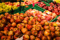 Bunch of red and green apples on boxes in supermarket Stock Images
