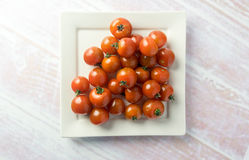 Bunch of red mini tomatoes on a plate Royalty Free Stock Photo