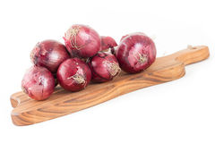 Bunch of red onions on wooden cutting board isolated on white ba Stock Photography
