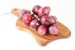 Bunch of red onions on wooden cutting board isolated on white ba Royalty Free Stock Image