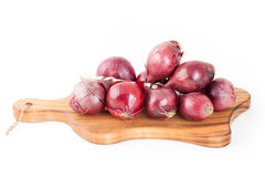 Bunch of red onions on wooden cutting board isolated on white ba Stock Photos