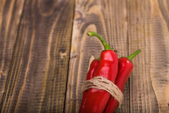 Bunch of red pungent peppers. Bunch of red pungent chili peppers with green tails tied by rope natural eco ingredient on wooden background closeup copyspace stock image