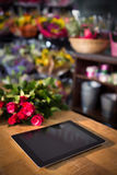 Bunch of red roses and digital tablet on the wooden table Royalty Free Stock Photos