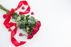 Bunch of red roses surrounded with heart shape chocolate. On white background Royalty Free Stock Photos
