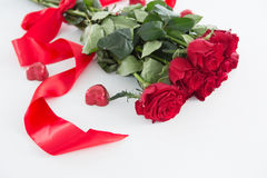 Bunch of red roses surrounded with heart shape chocolate. On white background Stock Photos