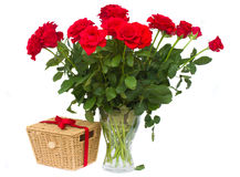 Bunch of red roses in vase with gift basket Stock Photos