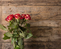 Bunch of red roses in vase on wooden background Royalty Free Stock Images
