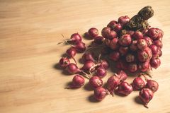 Bunch of Red Shallots onions. Bunch of Red Shallots onions on wooden table with high contrast picture style stock image