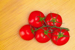 Bunch of red tomatoes on wooden table - close up studio shot Royalty Free Stock Photography