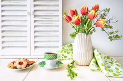 Bunch of red tulips, espresso in green cup with white dots and c Stock Image