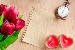 Bunch of red tulips and an paper diary. Bunch of red tulips and an paper diary made from recycle paper on wooden background Royalty Free Stock Image