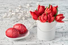 Bunch of red tulips and two red Easter eggs on white background Stock Photos