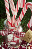 Bunch of red and white striped candy canes in glas. S jar on christmas background. Close up Stock Photo
