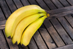 Bunch of ripe bananas. Bunch of delicious ripe yellow bananas lying on a rustic slatted wooden table royalty free stock photography