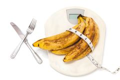 Bunch of bananas lying on floor scales on white background Stock Photo
