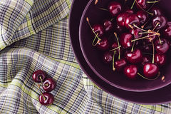 Bunch ripe cherry in purple plate on plaid background. Stock Image